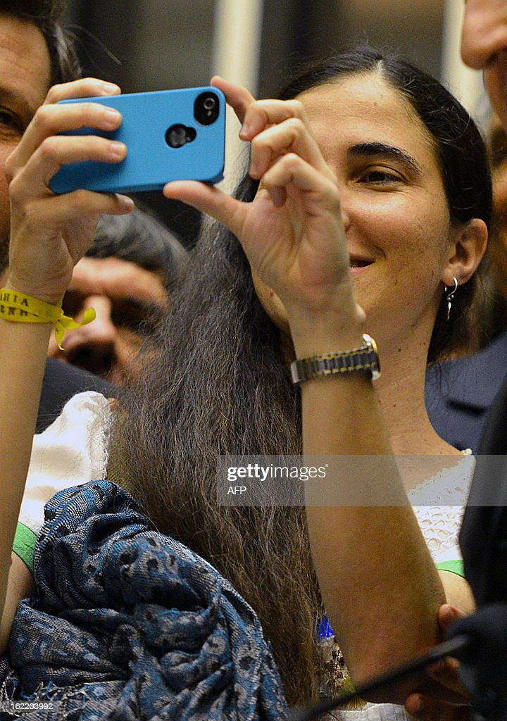 Dissident Cuban blogger Yoani Sanchez takes pictures during her visit to the Chamber of Deputies, at the National Congress in Brasilia, on February 20, 2013. Sanchez is on an 80-day tour, after she got a passport two weeks ago under Cuba's sweeping immigration reform that went into effect this year. The 37-year-old philologist, who found an international audience on the Internet with her prize-winning blog 'Generation Y,' is known for her biting commentary, which has drawn the displeasure of Cuba's ruling communist party. AFP PHOTO/Pedro LADEIRA
