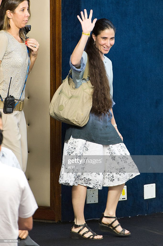 Dissident Cuban blogger Yoani Sanchez waves to the audience before a debate in Sao Paulo, Brazil, on February 21, 2013. Sanchez is on an 80-day tour, after she got a passport two weeks ago under Cuba's sweeping immigration reform that went into effect this year. The 37-year-old philologist, who found an international audience on the Internet with her award-winning blog 'Generation Y,' is known for her biting commentary, which has drawn the displeasure of Cuba's ruling communist party. AFP PHOTO/Yasuyoshi CHIBA
