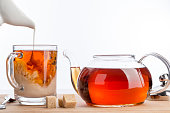 Dissolve milk in a cup of black tea. Transparent teapot and cup with three cubes of brown sugar on white background