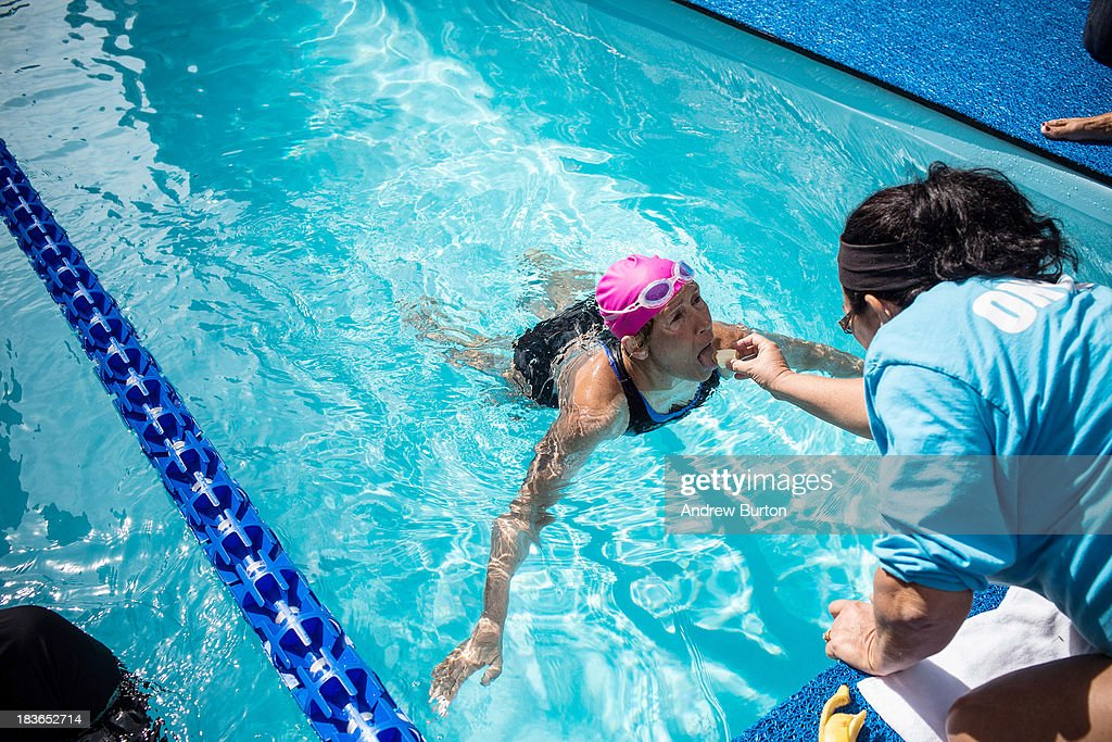 Distance swimmer <a gi-track='captionPersonalityLinkClicked' href=/galleries/search?phrase=Diana+Nyad&family=editorial&specificpeople=678501 ng-click='$event.stopPropagation()'>Diana Nyad</a> (R) is fed a banana by support staff during her attempt to swim for 48 hours straight in a constructed 40-meter pool in Herald Square, to support victims of Hurricane Sandy on October 8, 2013 in New York City. In August 2013 Nyad, age 64, swam non-stop from Florida to Cuba without a shark cage, a distance of approximately 110 miles, in approximately 53 hours. Nyad will swim with partners throughout the 48 hour challenge, and will be visited by various athletes and celebrities, too.