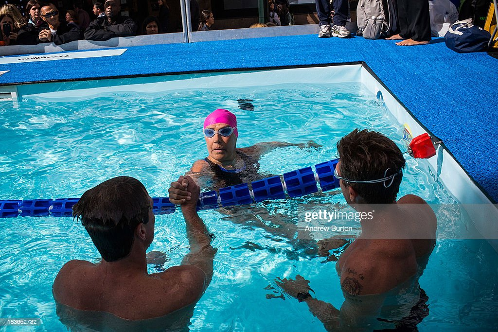 Distance Swimmer <a gi-track='captionPersonalityLinkClicked' href=/galleries/search?phrase=Diana+Nyad&family=editorial&specificpeople=678501 ng-click='$event.stopPropagation()'>Diana Nyad</a> (C) meets volunteer swim partners from the Fire Department of New York (FDNY) during an attempt to swim for 48 hours straight in a constructed 40-meter pool in Herald Square, to support victims of Hurricane Sandy on October 8, 2013 in New York City. In August 2013 Nyad, age 64, swam non-stop from Florida to Cuba without a shark cage, a distance of approximately 110 miles, in approximately 53 hours. Nyad will swim with partners throughout the 48 hour challenge, and will be visited by various athletes and celebrities, too.