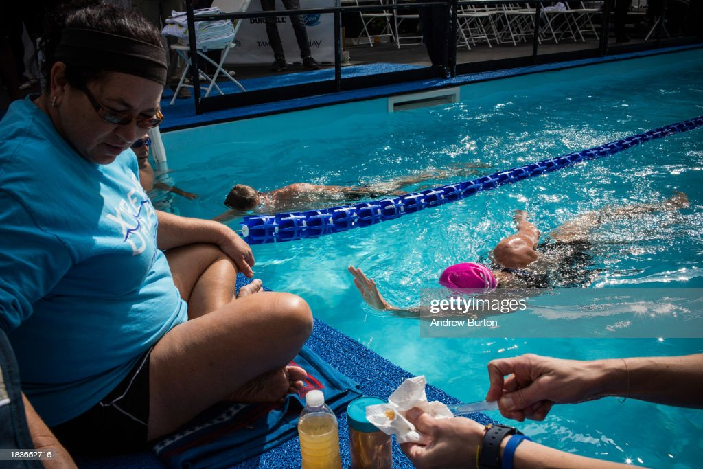 Distance Swimmer <a gi-track='captionPersonalityLinkClicked' href=/galleries/search?phrase=Diana+Nyad&family=editorial&specificpeople=678501 ng-click='$event.stopPropagation()'>Diana Nyad</a> (R) swims in a 40-meter pool, constructed in Herald Square, during an attempt to swim for 48 hours straight to support victims of Hurricane Sandy on October 8, 2013 in New York City. In August 2013 Nyad, age 64, swam non-stop from Florida to Cuba without a shark cage, a distance of approximately 110 miles, in approximately 53 hours. Nyad will swim with partners throughout the 48 hour challenge, and will be visited by various athletes and celebrities, too.