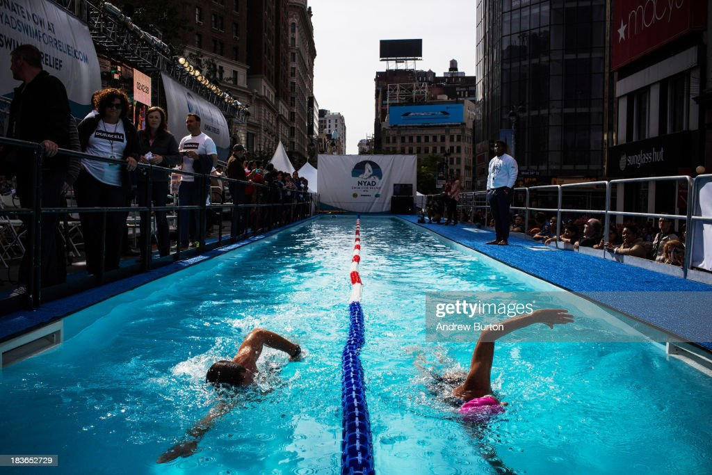 Distance Swimmer Diana Nyad (R) swims in a 40-meter pool, constructed in Herald Square, during an attempt to swim for 48 hours straight to support victims of Hurricane Sandy on October 8, 2013 in New York City. In August 2013 Nyad, age 64, swam non-stop from Florida to Cuba without a shark cage, a distance of approximately 110 miles, in approximately 53 hours. Nyad will swim with partners throughout the 48 hour challenge, and will be visited by various athletes and celebrities, too.
