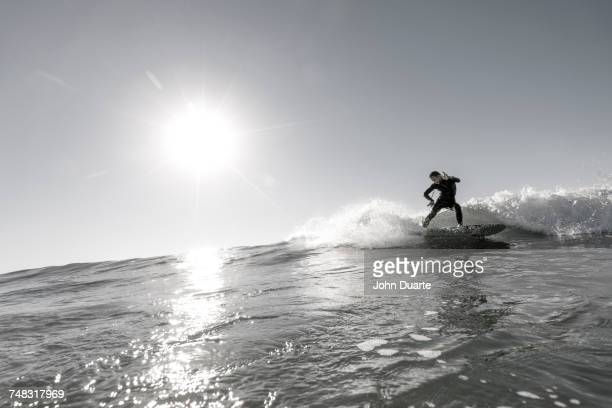 Distant Caucasian man surfing in sunny ocean