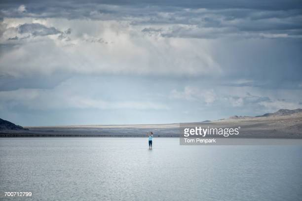 Distant Caucasian man wading in lake