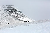 Single Figure Climbing a Snow Covered Mountain Ridge