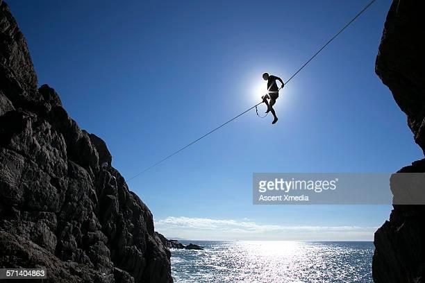 Distant man crosses highline above sea, coastline