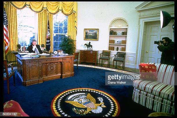Distant of Pres Bill Clinton talking on phone at desk in Oval Office