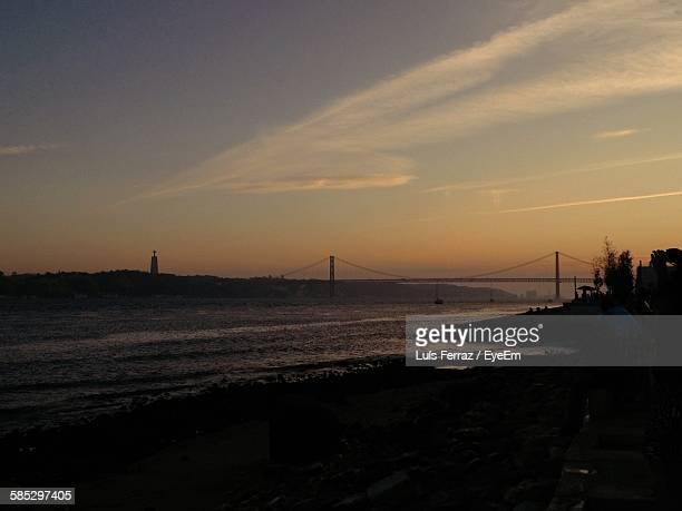 Distant View Of 25 De Abril Bridge Over Tejo River Against Sky During Sunset