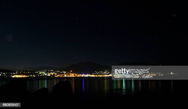 Distant View Of Illuminated City By Sea Against Sky At Night