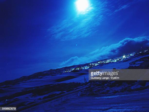 Distant View Of Illuminated City On Snow Covered Landscape