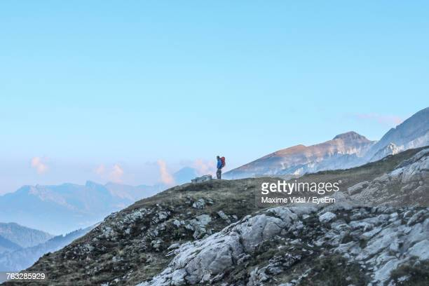 Distant View Of Male Hiker Standing On Cliff Against Blue Sky