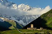 Distant view of old ruined Svanetian towers in valley, Ushguli village, Svaneti, Georgia