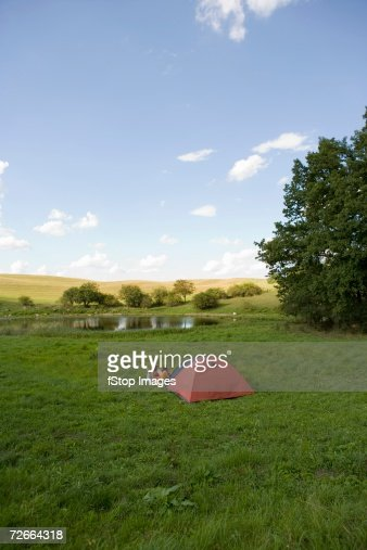 Distant view of people camping in field : Stock Photo