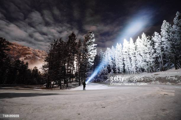 Distant View Of Person Showing Flashlight Towards Star Field At Night During Winter