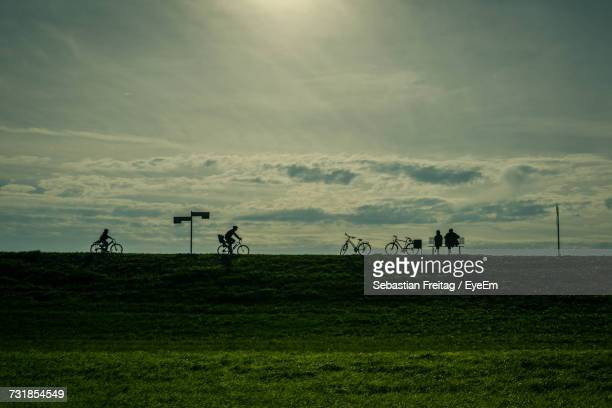 Distant View Of Silhouette People On Field Against Sky