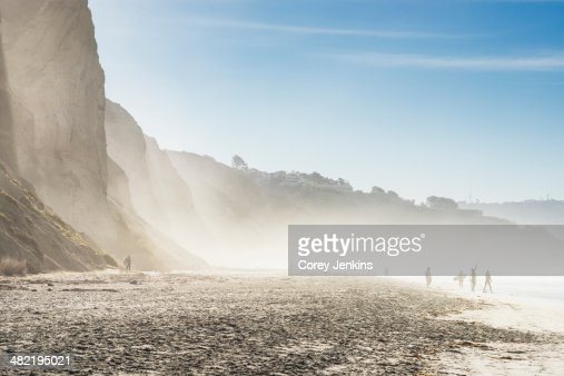 Distant view of surfers on misty beach, Black Beach, La Jolla, California, USA