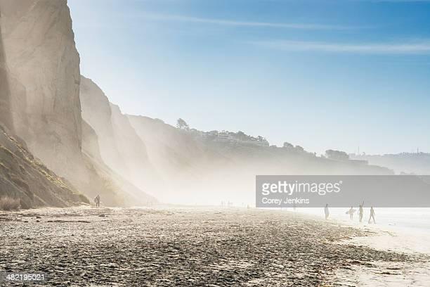 Distant view of surfers on misty beach, Black Beach, La Jolla, California, USA