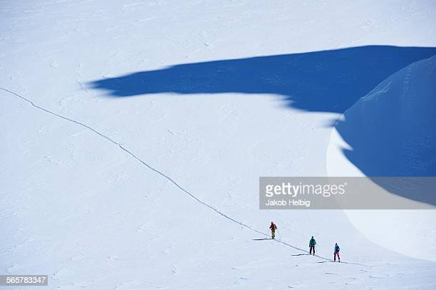 Distant view of three skiers on track, Mont Blanc massif, Graian Alps, France
