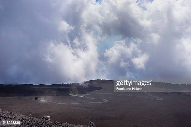 Distant view of tour buses on winding road, Mount Etna, Catania, Sicily, Italy