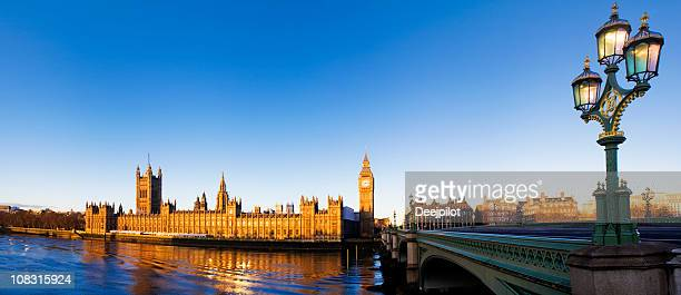 Distant view over water of Big Ben under clear blue sky.