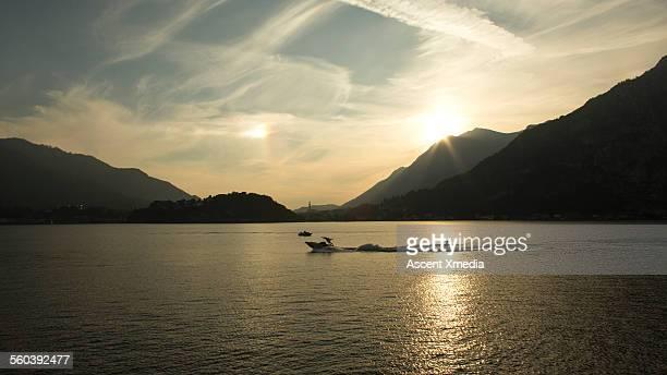 Distant waterskier tracks across tranquil lake