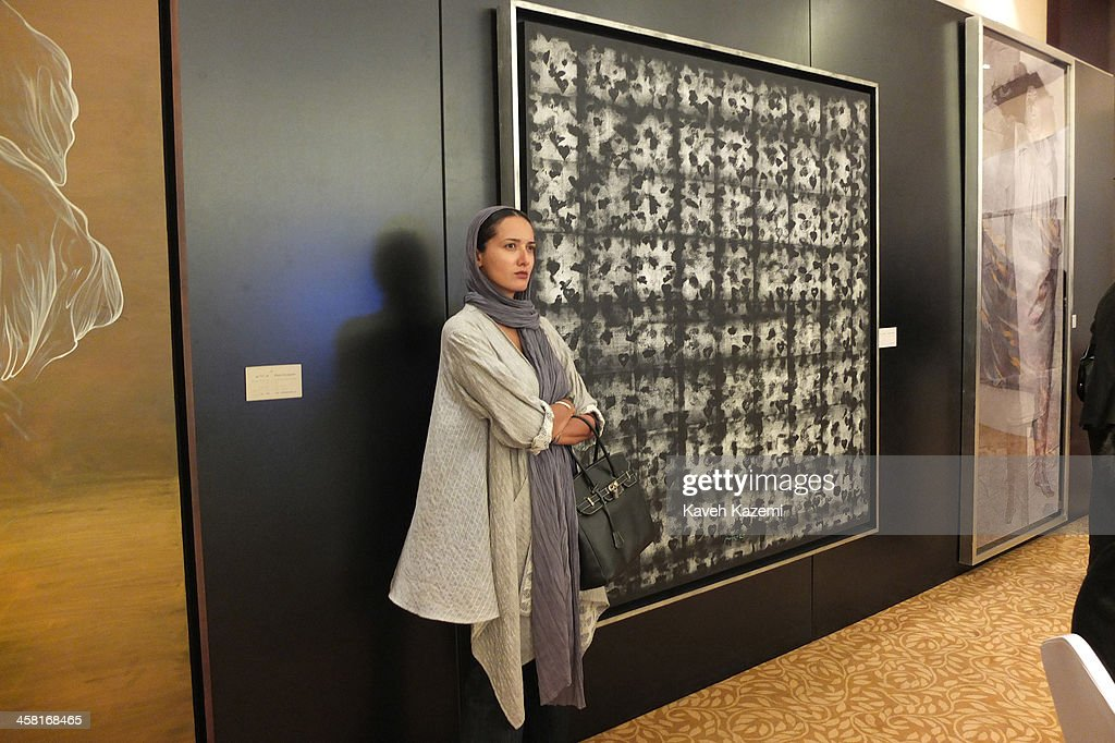 A distinguished looking female in modern clothing stands next to a framed paintiing on the wall during a contemporary art auction by famous Iranian artists in the dinning hall of hotel Azadi on June 28, 2013 in Tehran, Iran.