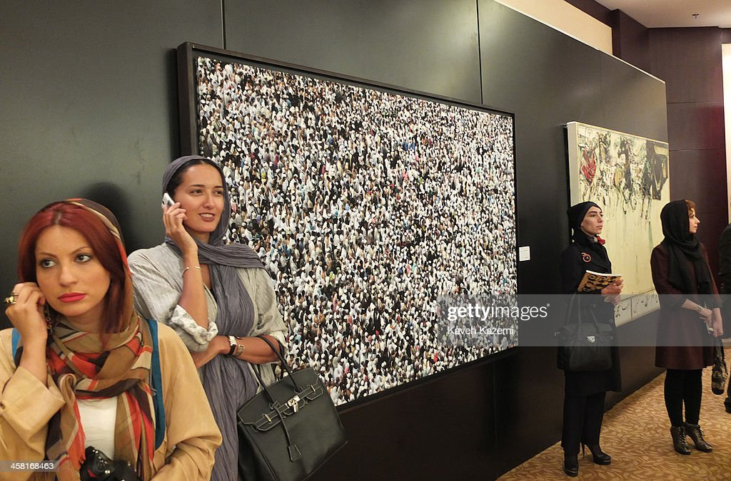 A distinguished looking female in modern clothing stands talking on her mobile phone next to a framed paintiing on the wall during a contemporary art auction by famous Iranian artists in the dinning hall of hotel Azadi on June 28, 2013 in Tehran, Iran.