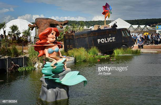 A distorted mermaid sculpture and a fountain by Banksy made from an abandoned police riot vehicle are displayed as Banksy's Dismaland Bemusement Park...