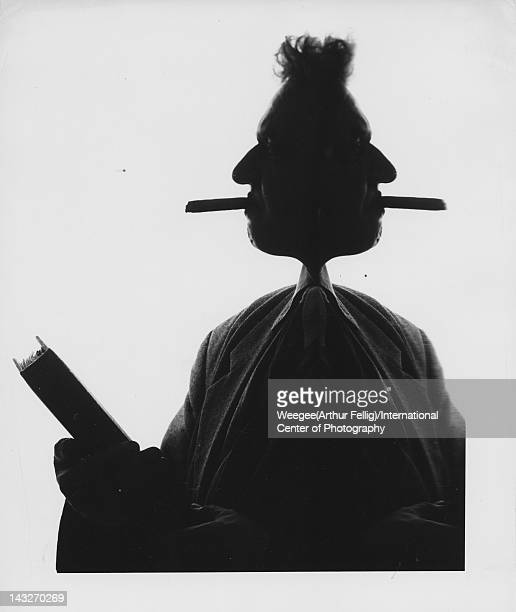 Distorted silhouette profile of American photographer Weegee with a cigar in his mouth as he holds a Holdon Binders Photo Album mid 1950s