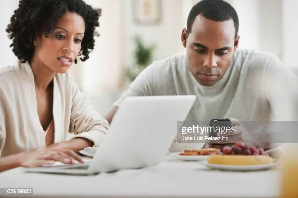 Distracted couple eating breakfast