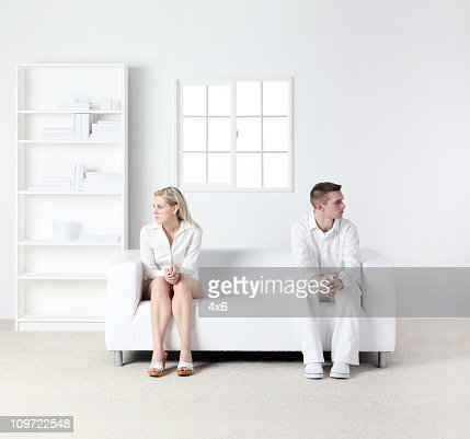 Distracted couple sitting on couch