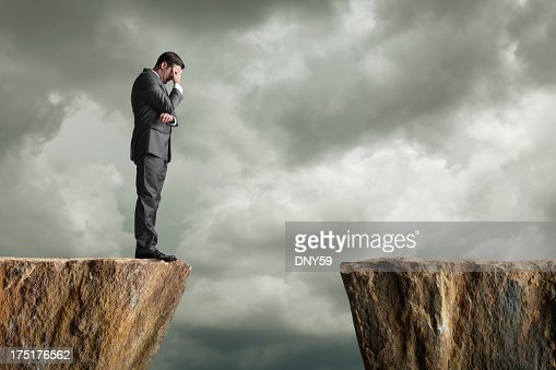 Distraught businessman standing at the edge of a cliff