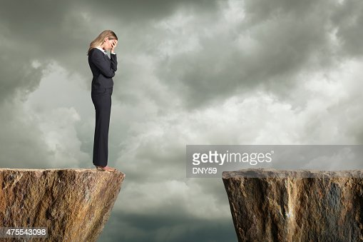 Distraught businesswoman standing at the edge of a cliff