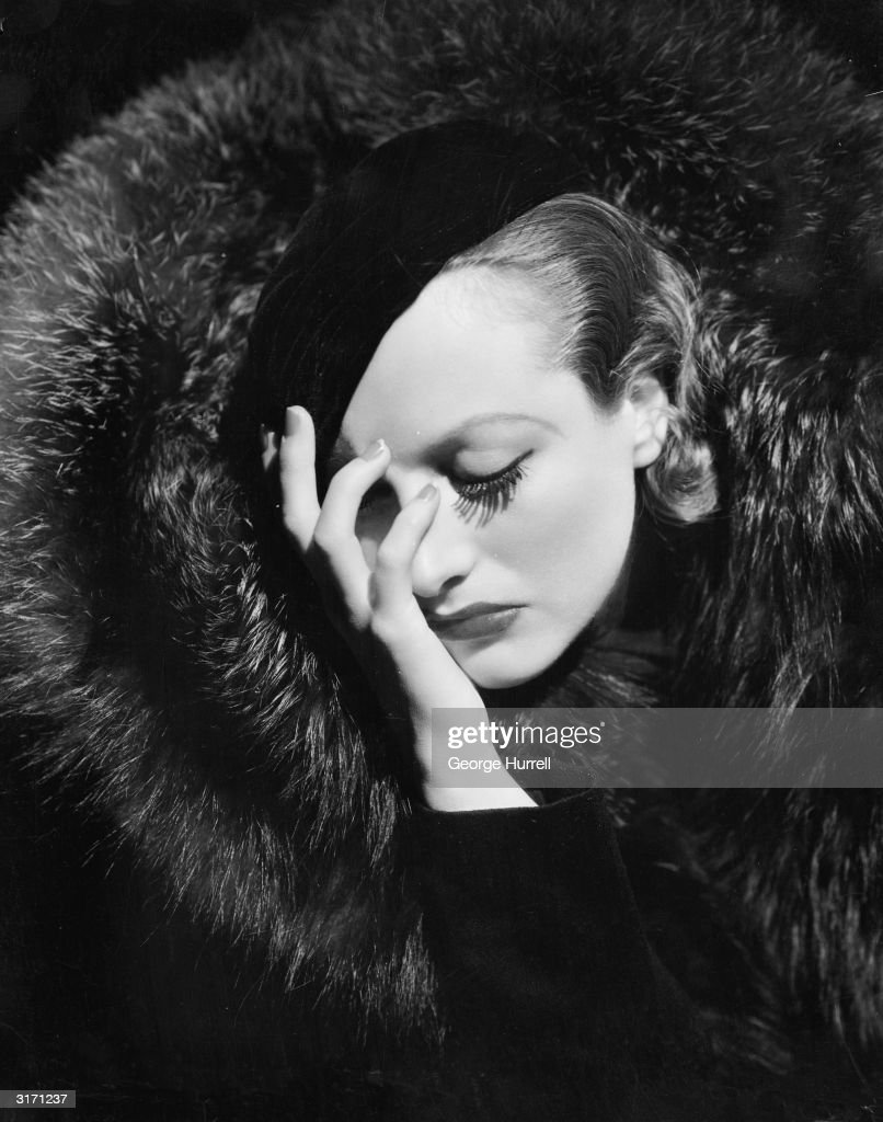 A distraught looking Joan Crawford wearing a beret and a large fur coat