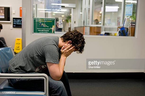 Distraught man sitting in a waiting room covering his face