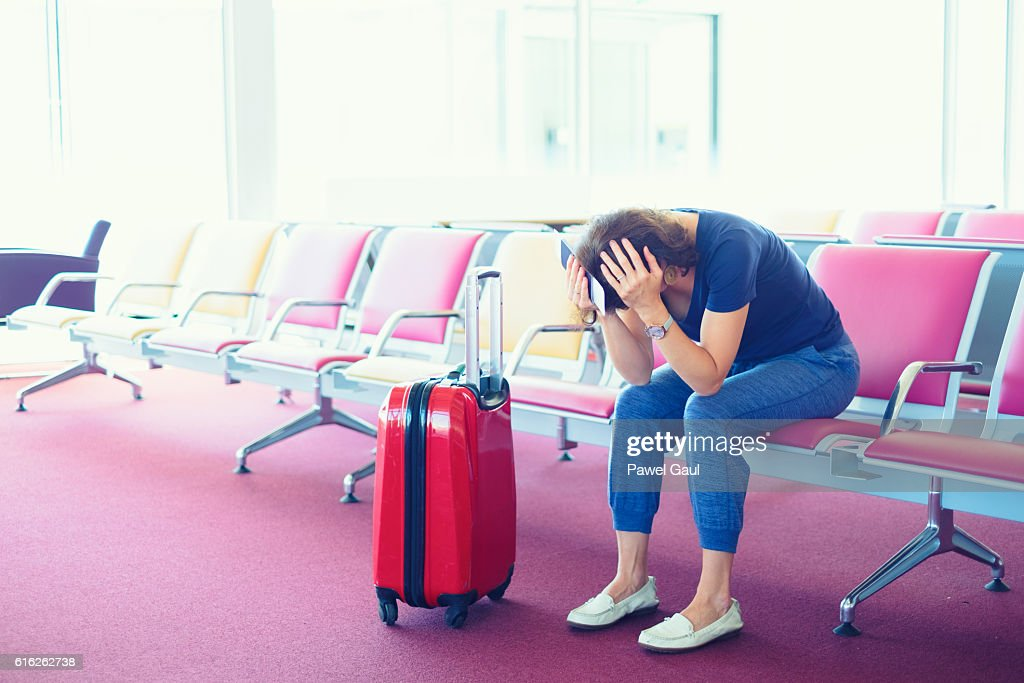 Distraught Woman stuck at airport : Stock Photo