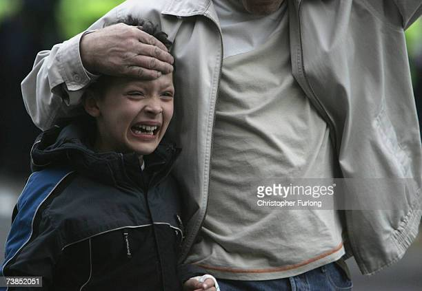 A distraught young fan is escorted into the stadium as trouble flares prior to the UEFA Champions League Quarter Final second leg match between...