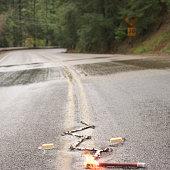 Distress flare on wet roadway warning motorists of washout ahead