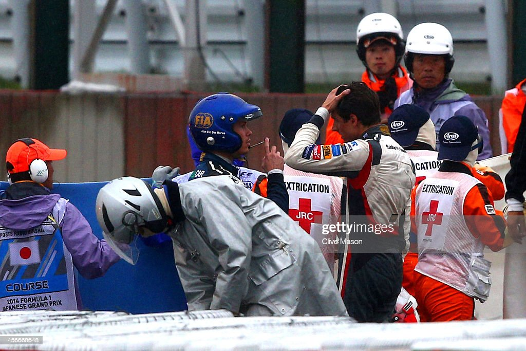 A distressed <a gi-track='captionPersonalityLinkClicked' href=/galleries/search?phrase=Adrian+Sutil&family=editorial&specificpeople=750787 ng-click='$event.stopPropagation()'>Adrian Sutil</a> (C) of Germany and Sauber F1 speaks to a Doctor whilst Jules Bianchi of France and Marussia receives urgent medical attention following a crash during the Japanese Formula One Grand Prix at Suzuka Circuit on October 5, 2014 in Suzuka, Japan.