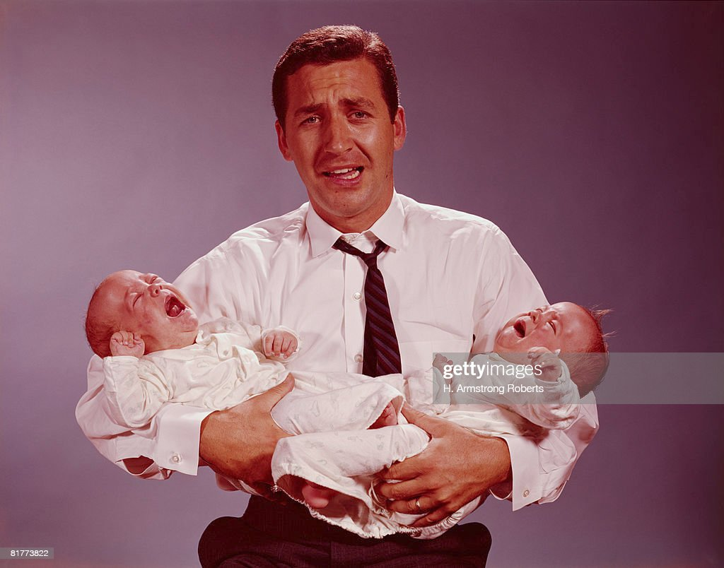 Distressed looking father holding crying twin babies in his arms. (Photo by H. Armstrong Roberts/Retrofile/Getty Images) : Stock Photo