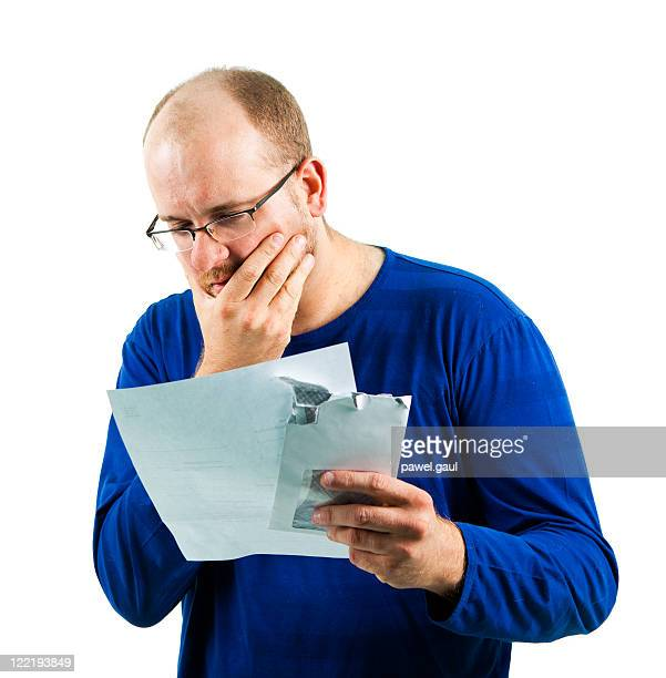 Distressed man holding bill, isolated on white.