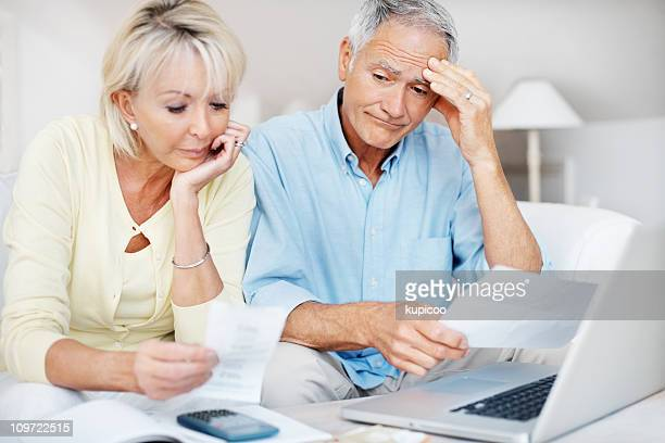 Distressed mature couple angry with so many bills to pay