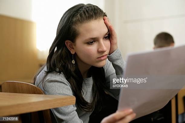 Distressed teenage girl holding an sheet of paper