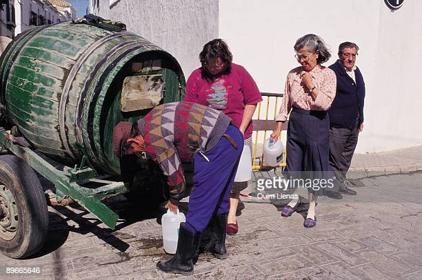 Distribution of water in utrera for drought People filling drums of water of a barrel in a street of Utrera during the drought in Andalusia