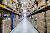 Color image of distribution warehouse in huge factory. Logistics, freight, shipping, receiving. No people, space for copy.