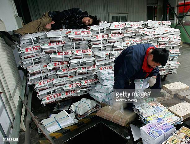 A distributor of Beijing Youth Daily drops newspapers through a duct down onto a waiting truck at a print factory on December 21 2004 in Beijing...