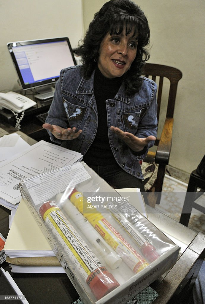 District attorney Abigail Saba, shows flares used during the Libertadores football match in which 14-year-old Kevin Beltran was killed after he was reached by a flare thrown by a supporter of Brazil Corinthians, in Oruro, 240 km southwest of La Paz, Bolivia on March 15, 2013. AFP PHOTO/Aizar RALDES