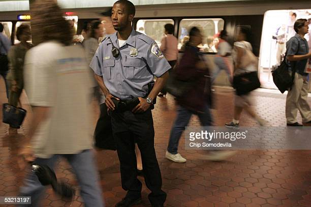 District of Columbia Metropolitan Police Officer D Charles keeps an eye on the morning rush hour passengers at the Metro Center subway stop July 8...