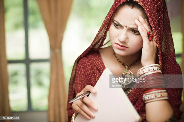 Disturbed newly married Indian, young woman holding pen and notepad.